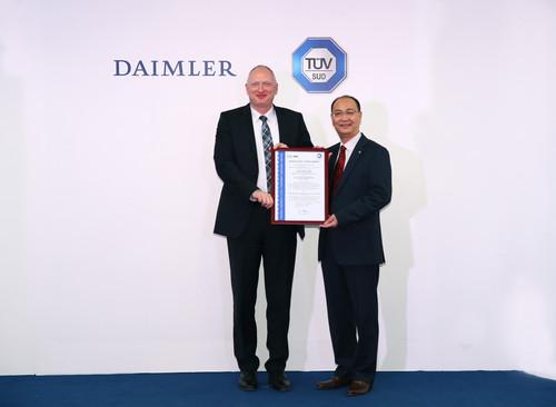Robert Veit (links), Präsident und CEO von Daimler Trucks and Buses China, nimmt die VDA-6.2-Zertifizierungsurkunde von Zhu Wencai, Senior Vice President von TÜV Greater China, entgegen.