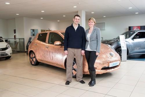 Brett Garner und seine Frau vor dem mit 100 000 Münzen verzierten Nissan Leaf.