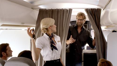 Jürgen Klopp schiebt den Vorhang der Business Class bei Seite, um von der Stewardess seinen Opel-Schlüssel zu bekommen.