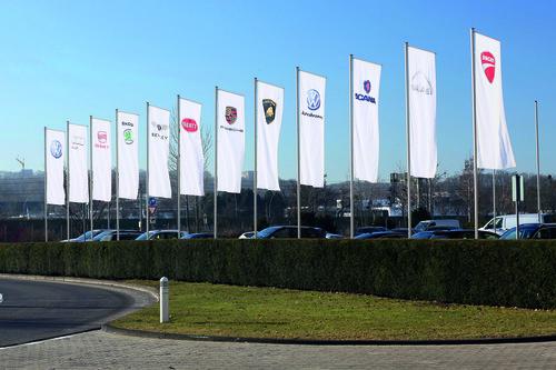 Fahnen der Konzernmarken vor dem Verwaltungshochhaus am VW-Stammsitz Wolfsburg.