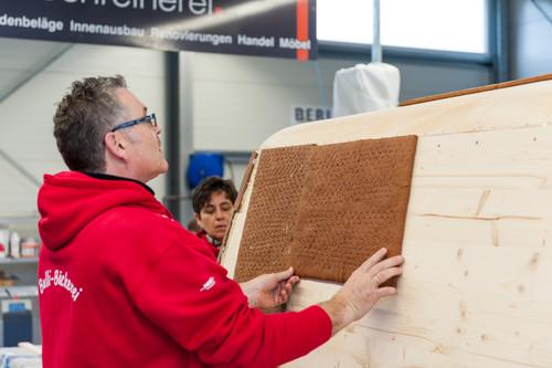 Initiator Rudi Dietl klebt eine Lebkuchenplatte auf die Holzkonstruktion des Bulli.