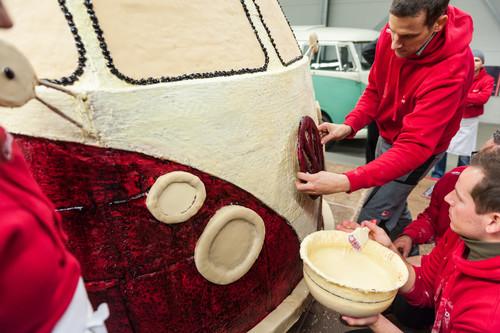 Helfer kleben mit weißer Schokolade das VW-Logo auf den Lebkuchen-Bulli.