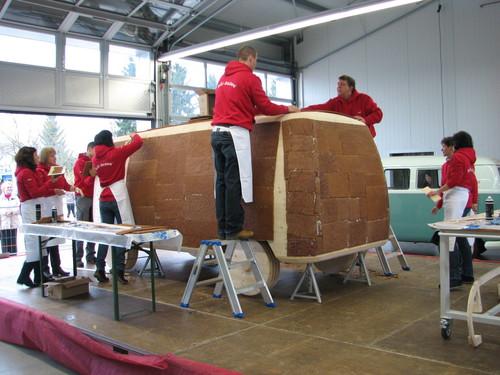 Fleißige Helfer kleben mit weißer Schokolade die Lebkuchen-Platten auf die Holzkonstruktion.