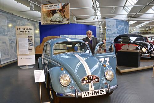 Hans Wehner (90) am Duplikat seines damals neuen 34-PS-Käfers. Darüber ist das Werbeplakat zu sehen, mit dem Volkswagen den Sieg Wehners bei der Tour d'Europe gewürdigt hat.