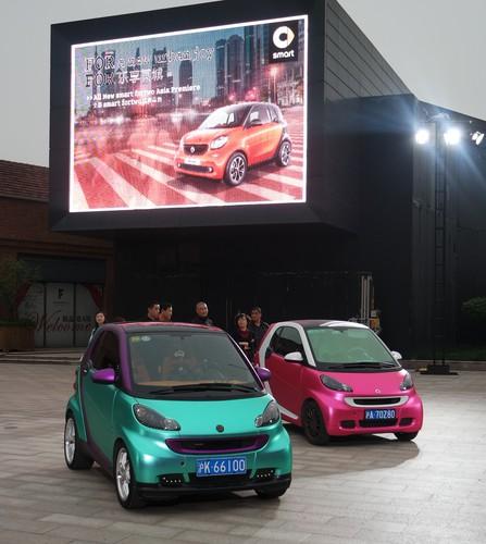 Alt und neu- das  bisherige Modell in Natura und in chinesischen Farben unter der Leinwand mit dem neuen Smart Fortwo.